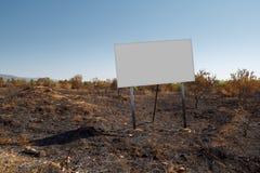 Tabellone per le affissioni in bianco nel suolo del fuoco Immagini Stock