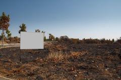 Tabellone per le affissioni in bianco nel suolo del fuoco Fotografia Stock