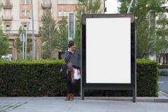 Tabellone per le affissioni e donna in bianco con il cellulare Immagini Stock