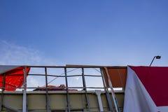 Tabellone per le affissioni lacerato che si sviluppa nell'aria contro il cielo blu fotografia stock libera da diritti