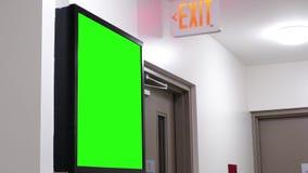 Tabellone per le affissioni verde per il vostro annuncio accanto al segno dell'uscita stock footage