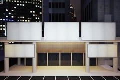 Tabelloni per le affissioni bianchi in bianco su costruzione moderna nel distretto urbano di notte Immagini Stock
