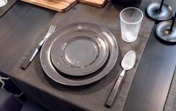 Tabelluppsättning för formellt äta middag på den svarta tabellen med svart porslin Arkivfoton