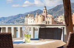 Tabelluppsättning i italiensk restaurang framme av den Camogli fjärden, near Ge Arkivbild