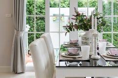 Tabelluppsättning på den glass dinning tabellen med vita stolar Royaltyfri Foto