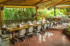 Tabelluppsättning på enfärgad terrass i en tropisk miljö Arkivfoto