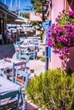 Taberna coloreada viva griega tradicional en la calle mediterránea estrecha en día de verano caliente imagenes de archivo