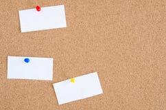 Tablón de anuncios con las hojas de papel en blanco Fotos de archivo
