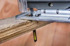 Tablón de madera del corte con la herramienta eléctrica del rompecabezas Hoja de sierra en tablón fotografía de archivo