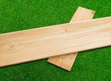 Tablón de madera en un fondo de la hierba verde Foto de archivo