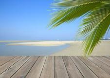 Tablón de madera sobre la playa con la palmera del coco Foto de archivo