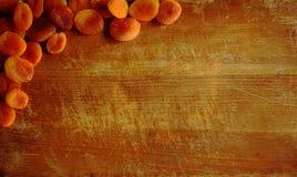 Tablón del corte de la cocina con los albaricoques secados imagen de archivo