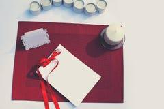 Tabla adornada celebradora con la tarjeta de papel y las velas Imagen de archivo