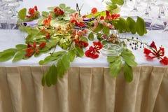 Tabla adornada con las flores exóticas Imagenes de archivo