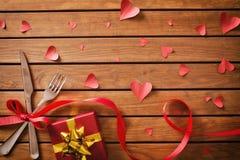 Tabla adornada con los ornamentos rojos para el día de tarjetas del día de San Valentín con el regalo foto de archivo libre de regalías