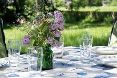Tabla adornada del jardín a comer afuera en el comienzo del verano Imágenes de archivo libres de regalías