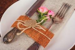 Tabla adornada para cenar en estilo rústico con las rosas rosadas Imagen de archivo libre de regalías