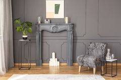 Tabla al lado de la butaca gris en interior elegante de la sala de estar con Imagenes de archivo