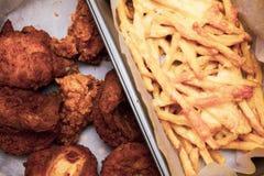 Tabla antedicha de la endecha plana con las alas de pollo frito y las patatas fritas en la caja Comida malsana servida Comida de  fotos de archivo