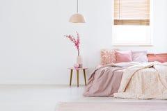 Tabla antedicha de la lámpara con las flores en los wi interiores del dormitorio en colores pastel rosado Foto de archivo