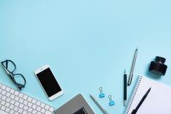 Tabla azul del escritorio de oficina con el cuaderno en blanco, el smartphone, el teclado de ordenador y otros materiales de ofic fotografía de archivo