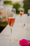 Tabla blanca adornada con la servilleta rosada y un vidrio de vino espumoso Fotos de archivo libres de regalías