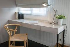 Tabla blanca con la silla de madera y libros en zona de trabajo moderna Fotografía de archivo libre de regalías