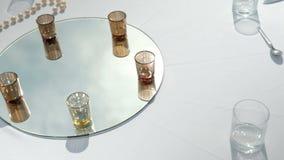 Tabla blanca con las bebidas en el espejo para el banquete en el aire fresco al aire libre almacen de metraje de vídeo