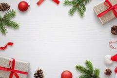 Tabla blanca con las decoraciones de la Navidad y espacio en el centro para el texto La composición con los regalos, abeto de la  Imágenes de archivo libres de regalías