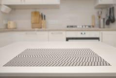 Tabla blanca con una servilleta en el fondo de una cocina borrosa imagen de archivo libre de regalías