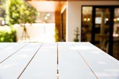 Tabla blanca de madera vacía y parte posterior borrosa del café o de la luz del restaurante fotos de archivo libres de regalías
