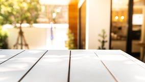 Tabla blanca de madera vacía y parte posterior borrosa del café o de la luz del restaurante foto de archivo libre de regalías