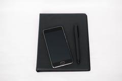 Tabla blanca del escritorio de oficina con el ordenador portátil, el smartphone, el cuaderno y la pluma Foto de archivo libre de regalías