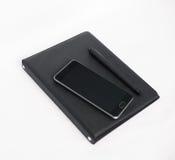 Tabla blanca del escritorio de oficina con el ordenador portátil, el smartphone, el cuaderno y la pluma Imagen de archivo libre de regalías