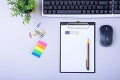 Tabla blanca del escritorio de oficina con el ordenador portátil, el smartphone, el cuaderno, el plan, y los vidrios Visión super Foto de archivo libre de regalías