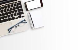 Tabla blanca del escritorio de oficina con el ordenador portátil y el teléfono elegante Imágenes de archivo libres de regalías