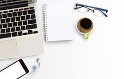Tabla blanca del escritorio de oficina con el ordenador portátil y el teléfono elegante Imagen de archivo