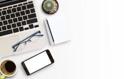 Tabla blanca del escritorio de oficina con el ordenador portátil y el teléfono elegante Fotos de archivo