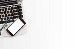 Tabla blanca del escritorio de oficina con el ordenador portátil y el teléfono elegante Fotografía de archivo libre de regalías