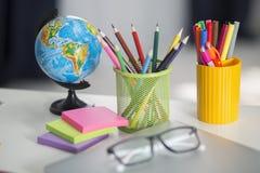 Tabla blanca del escritorio de oficina con los accesorios de la escuela con los materiales de oficina Foto de archivo libre de regalías