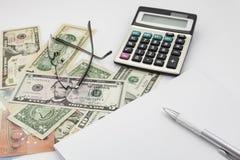 Tabla blanca del escritorio de oficina con los vidrios y el billete de banco de la calculadora de la pluma Foto de archivo