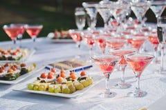 Tabla con bocados y una pirámide de los vidrios del champán Foto de archivo libre de regalías