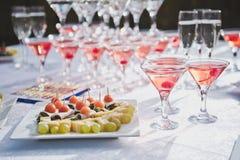 Tabla con bocados y una pirámide de los vidrios del champán Imágenes de archivo libres de regalías