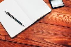 Tabla con el cuaderno, el smartphone y la pluma Fotografía de archivo