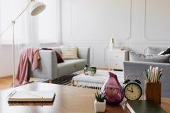 Tabla con el cuaderno, la pequeña planta en pote, el florero de cristal, el reloj y los lápices en la taza, foto real con el espa fotografía de archivo