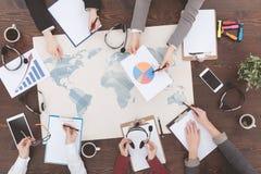 Tabla con el mapa del mundo, los diagramas y los auriculares Fotos de archivo libres de regalías