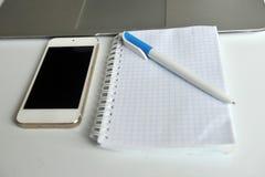 Tabla con el ordenador portátil, el smartphone, el cuaderno y la pluma Fotos de archivo libres de regalías