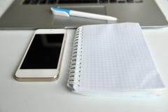 Tabla con el ordenador portátil, el smartphone, el cuaderno y la pluma Fotos de archivo
