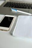 Tabla con el ordenador portátil, el smartphone, el cuaderno y la pluma Fotografía de archivo libre de regalías