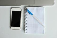Tabla con el ordenador portátil, el smartphone, el cuaderno y la pluma Foto de archivo